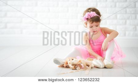 little child girl dreams of becoming ballerina with ballet shoes and pointe shoes in a pink tutu skirt poster