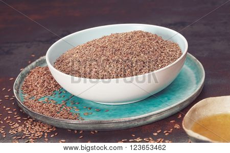 Flax seeds or linseed and oil. Whole and ground flax seed with linseed oil. Macro, selective focus, vintage toned image