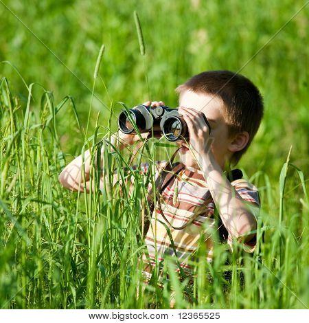 Jongen in een veld op zoek door middel van verrekijkers