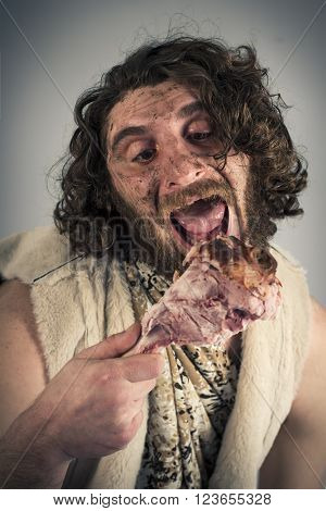 Silly hungry cave man eating ham on the bone