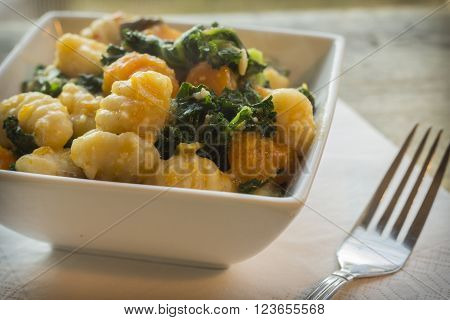Vegetarian gnocchi dish with squash kale and mushrooms poster
