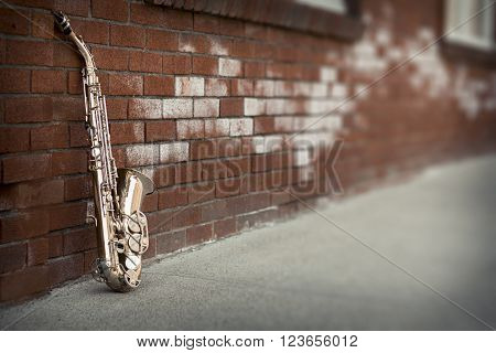 Jazz musical instrument saxophone with grungy street background poster