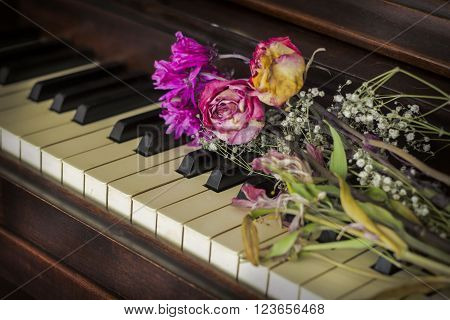 Old piano with dried roses atop the keys