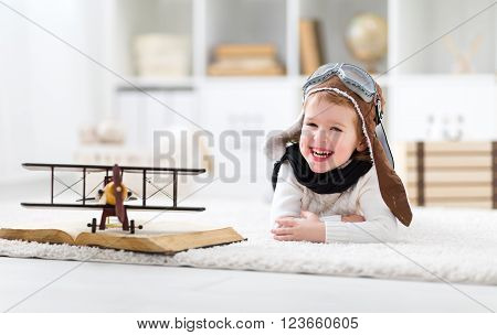 concept of children's dreams and travels. Happy pilot aviator child with a toy airplane plays at home in his room