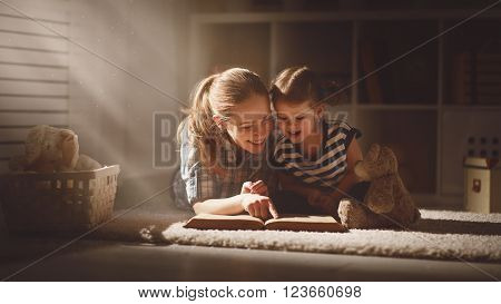 happy family mother and daughter read a book in the evening at home ** Note: Soft Focus at 100%, best at smaller sizes