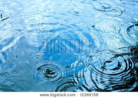 Rain drops rippling in a puddle with blue sky reflection