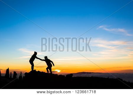 Teamwork couple helping hand trust help silhouette in mountains sunset. Team of climbers man and woman hikers help each other on top of mountain climbing together beautiful inspirational sunset landscape on Tenerife Canary Islands