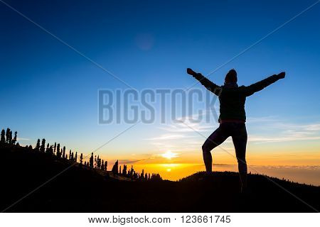 Woman hiker silhouette with arms outstretched in mountains. Female runner or climber looking at sunset view. Business concept and hands up enjoy inspirational landscape rocky trail footpath on Tenerife Canary Islands