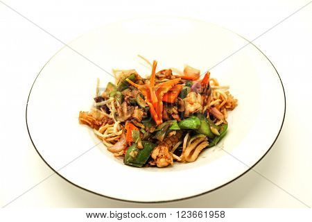 The Chinese fried noodles with squids, an octopus and vegetables