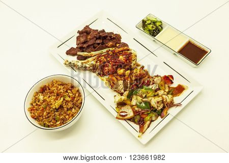 Surf and turf, fried lobster and juicy stake with a garnish from fried vegetables with with fried Chinese rice and hot sauces