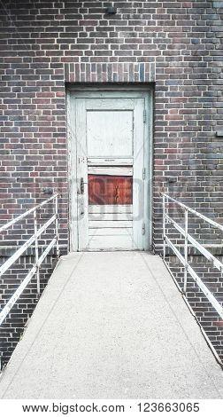 Broken door and handrail in an old black brick stone building