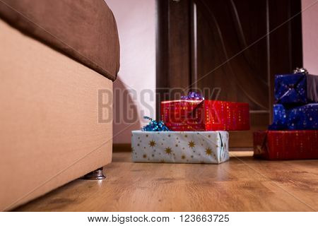 Pile of presents beside sofa. Birthday gifts in empty room. Where is the addressee. Boxes that bring joy.