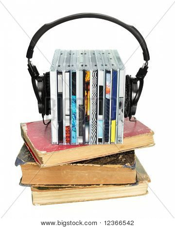 Stack of CDs with HI-Fi headphones and old books on white background