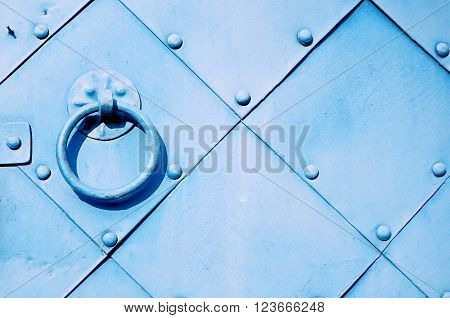 Old light blue door with rivets and aged metal door handle in the form of ring. Textured vintage background.