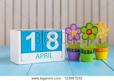 April 18th. Image of april 18 wooden color calendar on white background with flowers. Spring day, empty space for text. International Day For Monuments and Amateur Radio.