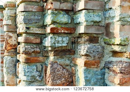 Old textured ribbed wall made of thin calcined brick known as plinfa - plinfa used in Byzantium and Ancient Rus construction. Vintage tones processing