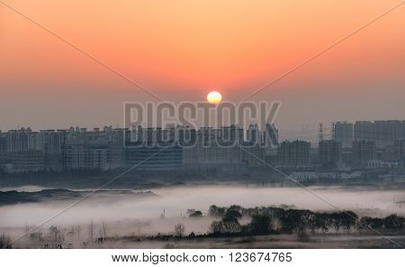 Sun rising behind the block of apartment in Shanghai China.