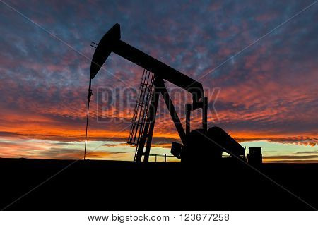 Dramatic sky over a pumpjack in rural Alberta Canada. These jacks can extract between 5 to 40 litres of crude oil and water emulsioin at each stroke.