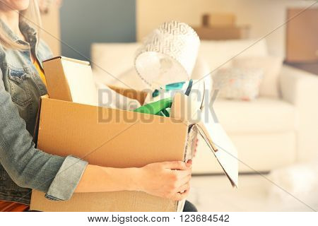 Young woman holding open cardboard box with things for moving into new house