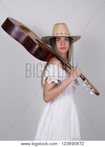 beautiful young leggy blond Country girl in a little white dress and cowboy hat with a guitar.