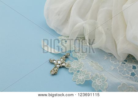 Close up of vintage baby baptism dress on blue background with cross
