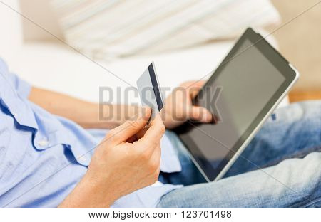 technology, people, online shopping, banking and lifestyle concept - close up of man with tablet pc computer and credit or bank card at home