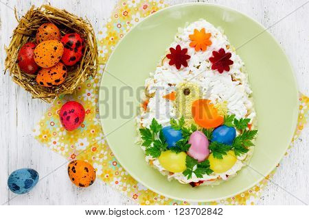 Easter egg salad. Thematic layered salad in the shape of egg with cute chick and colorful eggs top view.