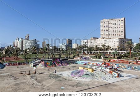 DURBAN SOUTH AFRICA - MARCH 23 2016: Many unknown childred skate boarding at colorful skate board park against city skyline on beachfront in Durban South Africa