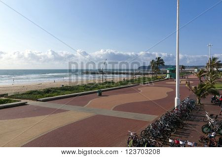 DURBAN SOUTH AFRICA - MARCH 23 2016: Early morning view of beach and promenade and cycle hire shop on Golden Mile beachfront in Durban South Africa