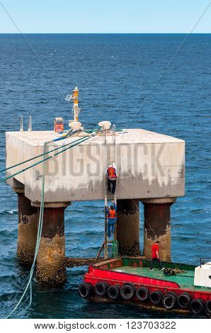 Puerto Madryn Argentina - December 13 2012: Dock workers climb on the mooring platform to Casting off in harbor of Puerto Madryn Patagonia Argentina South America