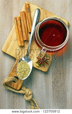 A cup of tea with spices on a wooden board copy space on a wooden background.