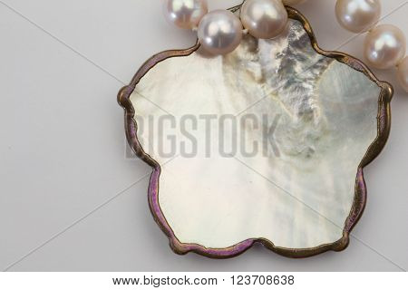 Close up pearl necklace and mother of pearl metal edged pendant isolated on white