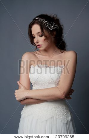 Adorable young bride with brown curly hair blue eyes and white dress and pearl headpiece with bare shoulders