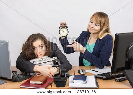 The Girl In The Office With A Smile, Holding A Clock And Looking At The Tormented Colleague