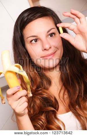 A young woman holding a supplement pill in one hand and a banana in the other.