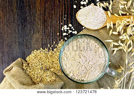 Oat Flour in a glass bowl, bran flakes in a spoon, oats and oatmeal stalks on sackcloth background on wooden board