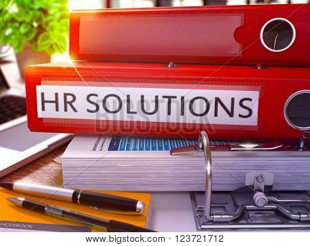 Red Ring Binder with Inscription HR - Human Resource - Solutions on Background of Working Table with Office Supplies and Laptop. HR Solutions Business Concept on Blurred Background. 3D Render.