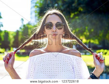 Beautiful young brunette student girl having fun with hair wearing glasses, joking kiss, resting enjoys fun, fashion style glamorous woman in a park in the summer outdoors. Close-up horizontal.