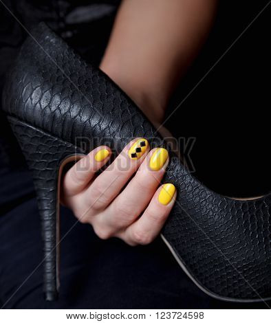 Close-up of extravagant yellow nails on a stiletto