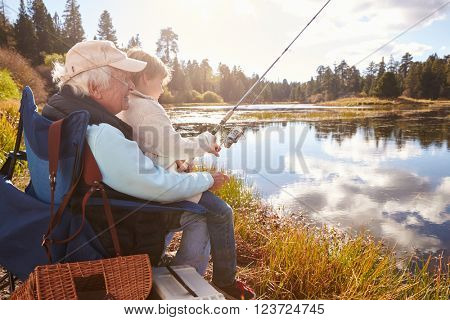 Senior man teaching his grandson to fish at a lake