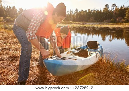 Father and son preparing kayak for launch from lakeside