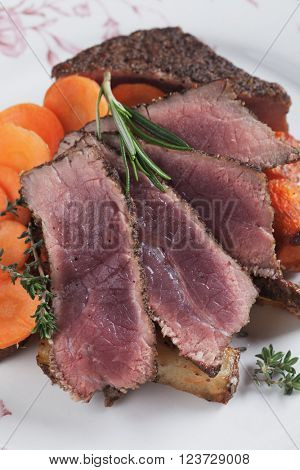Medium rare beef pepper steak with carrot, thyme and rosemary