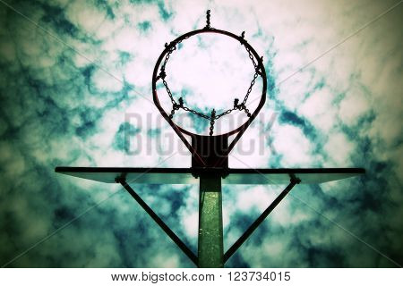 Old Neglect Basketball Backboard With Rusty Hoop Above Street Court. Blue Cloudy Sky In Bckground. R