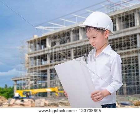 Asian boy pretend to be engineer at construction site