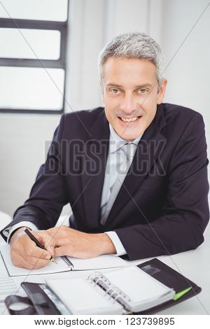 Portrait of happy businessman writing in spiral notebook at desk in office