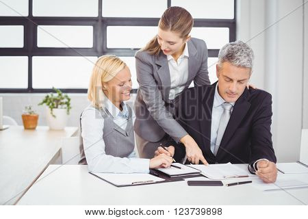 Business people explaining client with documents at desk in office