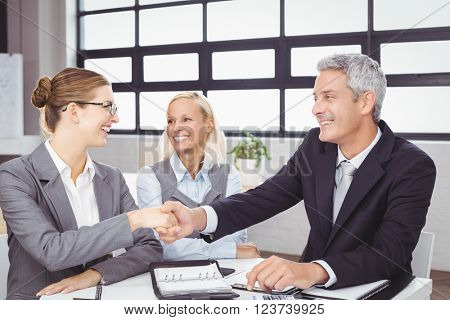 Happy business people handshaking during meeting at desk in office