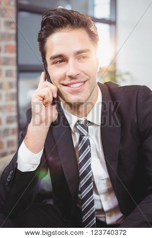 Close-up of handsome businessman talking on mobile phone in office