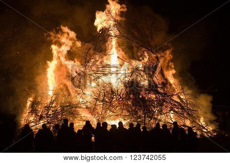 People are watching a huge bonfire a tradition with easter in North-West Europe.