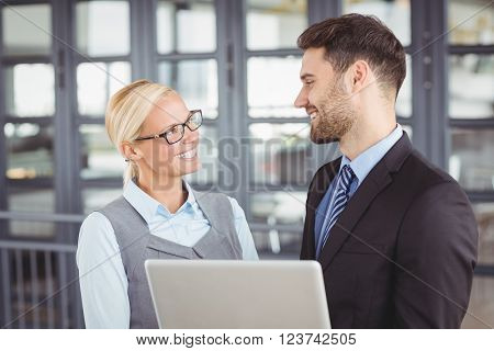 Happy business people looking face to face in office